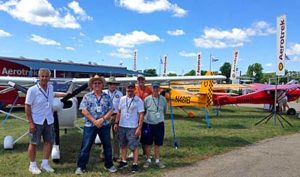 A few of the Aerotrek owners assisting at Aerotrek's AirVentrure 2016 pose in front of a group of airplanes representing many of of the popular model variations offered.